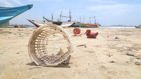 WELIGAMA, SRI LANKA - MARCH 2014: Trash washed up on shore in front of wooden fishing boast on beach. stock video footage