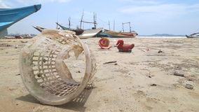 WELIGAMA, SRI LANKA - MARCH 2014: Trash washed up on shore in front of wooden fishing boast on beach. stock video