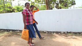 WELIGAMA, SRI LANKA - MARCH 2014: Two women walking down the street in Weligama with shopping bags. stock video