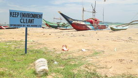 WELIGAMA, SRI LANKA - MARCH 2014: View of trash left on beach with traditional wooden fishing boats in background. stock video