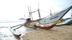 WELIGAMA, SRI LANKA - MARCH 2014: View of wooden fishing boats on beach. The term Weligama literally means 'sandy village' which r stock video