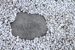 Welkom die tekenrots door witte rotsen wordt omringd Stock Afbeeldingen