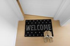 Welkom huis op zwarte mat Stock Foto's