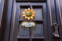 Welkom teken met bloem op de deur stock afbeelding