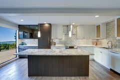 Modern kitchen room in a condo home. Well appointed kitchen features a large kitchen island, gray quartzite countertops, silver backsplash and white shaker royalty free stock photo