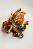 Well-browned and crisp duck confit with roast fennel, citrus fruit and prune sauce. Roasted Duck leg. White dish.  royalty free stock photography