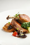 Well-browned and crisp duck confit with roast fennel, citrus fruit and prune sauce. Roasted Duck leg. White dish.  royalty free stock images