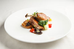 Well-browned and crisp duck confit with roast fennel, citrus fruit and prune sauce. Roasted Duck leg. White dish.  royalty free stock photos