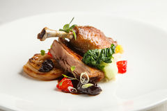 Well-browned and crisp duck confit with roast fennel, citrus fruit  prune sauce. Roasted  leg. White dish Stock Images