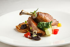 Well-browned and crisp duck confit with roast fennel, citrus fruit  prune sauce. Roasted  leg. White dish Stock Image