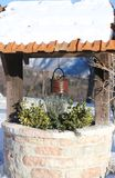 Well with bucket and snow on the roof in mountain village Stock Image