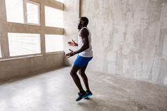 Well-built african guy making warm-up exercises royalty free stock photos