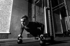 Well built brutal sportsman working out with kettlebells. Kettlebell training. Well built brutal professional sportsman holding kettlebells and doing push ups Stock Images