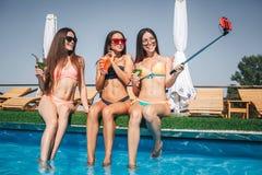 Well-built en positieve jonge vrouwen zitten bij rand van zwembad Zij stellen en glimlachen Het model op recht neemt selfie royalty-vrije stock fotografie
