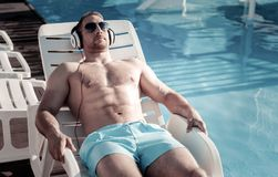 Well built gentleman sunbathing while lying on sunbed. Favorite leisure activity. Relaxed young man listening to music playing on her headphones and dreaming Royalty Free Stock Photography