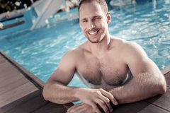 Well built millennial guy smiling while swimming in pool stock image