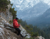 Well built mountain guide having rest at astonishing winter rocky landscape background Royalty Free Stock Photos