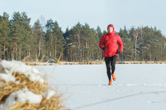 Well built running man outdoors in winter snowy forest Stock Photography