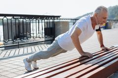 Well-built senior man doing push-ups from bench. Exercising power. Athletic senior man doing push-ups from the bench while working out in the waterfront area in Royalty Free Stock Photography