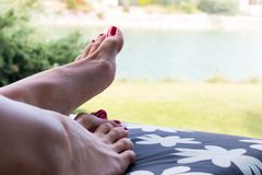 Well cared feet of sunbathing woman laying on deck chair close up with nature background stock photos