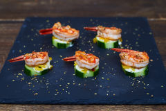 Well-cooked aromatic shrimps on grilled zucchinis with white sau Stock Photo
