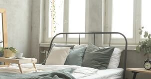 Well decorated bedroom morning. Bed with green coverlet stands in bright bedroom with large French windows mirror and small bedside lamp with a plant and alarm stock footage