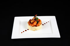 Well dish with prawns in white plate. On black background Royalty Free Stock Photo