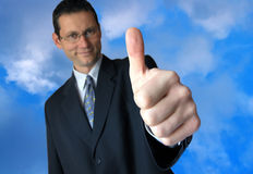 Well done!!!. Smiling businessman giving a thumbs up royalty free stock photo
