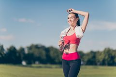Well done! Attractive young sportwoman finished her work out and. Now drinking water and smiling. She is outside on a summer stadium, with a towel on her stock images