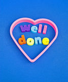Well done : congratulations. A macro image of the message well done in lower case text surrounded by a purple heart on a plain blue background. A concept image royalty free stock image