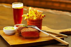 Well-done grilled marinated beef flank steak with ketchup, mustard and french fries with a glass of beer, with a fork. Over the meat on wooden board stock photography
