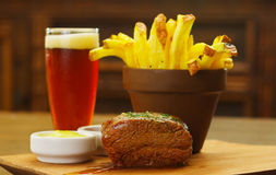 Well-done grilled marinated beef flank steak with ketchup, mustard and french fries with a glass of beer on wooden board.  royalty free stock images