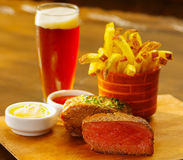 Well-done grilled marinated beef flank steak with ketchup, mustard, french fries and a glass of beer on wooden board.  royalty free stock photos