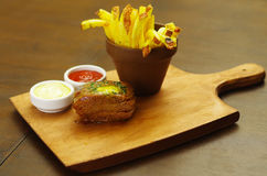 Well-done grilled marinated beef flank steak with ketchup, mustard and french fries on wooden board.  stock photo