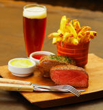 Well-done grilled marinated beef flank steak with a romero spice, ketchup, mustard, french fries and a glass of beer on. Wooden board stock image