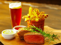 Well-done grilled marinated beef flank steak with a romero spice, ketchup, mustard, french fries and a glass of beer on. Wooden board stock images