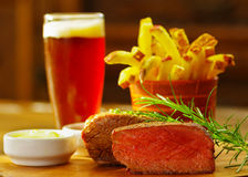 Well-done grilled marinated beef flank steak with a romero spice, ketchup, mustard, french fries and a glass of beer on. Wooden board royalty free stock photography