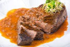 Well-done grilled marinated beef flank steak with sauce on plate royalty free stock photo