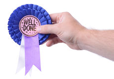Well done. A hand presenting a well done badge isolated on white stock photo