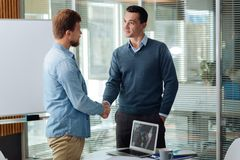 Attentive manager welcoming new partner. Well done. Handsome men keeping left hand in the pocket and wrinkling forehead while communicating with his friend Royalty Free Stock Photo