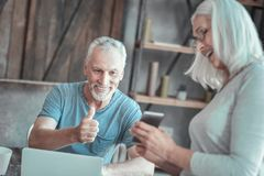 Happy unshaken man smiling and gesticulating. Well done. Happy unshaken aged men smiling by the table working with the laptop and gesticulating Royalty Free Stock Photography