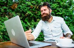 Well done. Hipster busy with freelance. Wifi and laptop. Drink coffee and work faster. Bearded man successful freelance stock photography