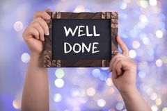 Well done sign. A woman holding chalkboard with words well done on bokeh light background royalty free stock photography