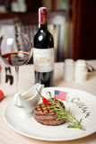 Well done steak and red wine. With spicy chilli sauce on the table Royalty Free Stock Photography