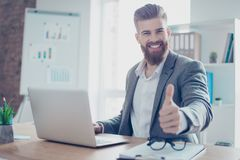 Well done! Successful happy businessman is showing thumb up. He. Is handsome, smiling, his company achieved the goal royalty free stock photo