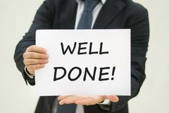 Well Done text on paper. Business man in suit holding a white sheet with a text on it: Well Done stock photo