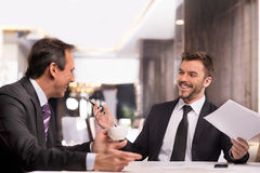 Well done!. Two cheerful business people in formalwear discussing something and smiling while sitting at the restaurant Royalty Free Stock Photography
