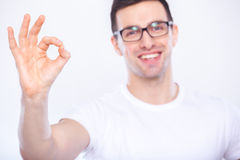 Well done!. A young man in glasses showing ok. White background Stock Photo