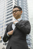 Well dressed asian business man adjusting his neck tie Royalty Free Stock Images