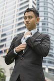 Well dressed asian business man adjusting his neck tie Stock Photography